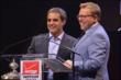 Emcee Leigh Diffey and Juan Pablo Montoya at the podium during the 2014 INDYCAR Championship Celebration -- Photo by: Chris Owens