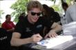Josef Newgarden signs some autographs during the INDYCAR Fan Village autograph session -- Photo by: Joe Skibinski