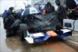 The Novo Nordisk Chip Ganassi team cover up Charlie Kimball's car during the rain delay -- Photo by: Chris Owens
