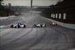 A pack of IndyCar drivers head into turn 1 at IMS -- Photo by: Bret Kelley