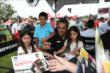 Young fans of Juan Pablo Montoya get a photo of the superstar in the INDYCAR Fan Village at Mid-Ohio -- Photo by: Chris Jones