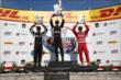 Will Power, Juan Pablo Montoya, and Tony Kanaan hoist their trophies on the podium following the ABC Supply Wisconsin 250 at the Milwaukee Mile -- Photo by: Chris Jones
