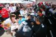 Juan Pablo Montoya gives a high-five during the autograph session in the INDYCAR Fan Village at Pocono Raceway -- Photo by: Bret Kelley