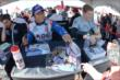 Takuma Sato and Josef Newgarden sign some autographs in the INDYCAR Fan Village -- Photo by: Chris Owens