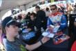 Teammates Carlos Huertas and Justin Wilson sign autographs in the INDYCAR Fan Village -- Photo by: Chris Owens