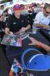 Scott Dixon signs an autograph for a young fan in the INDYCAR Fan Village -- Photo by: Chris Owens