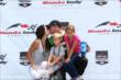 Sebastien Bourdais with a celebratory kiss from his wife on the podium -- Photo by: Chris Jones
