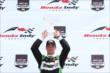 Sebastien Bourdais hoists his winner's trophy for Race 1 of the Honda Indy Toronto -- Photo by: Chris Jones
